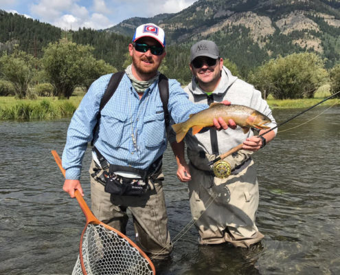 Fly fisherman and guide hold a cutthroat trout on Fish creek in jackson wyoming