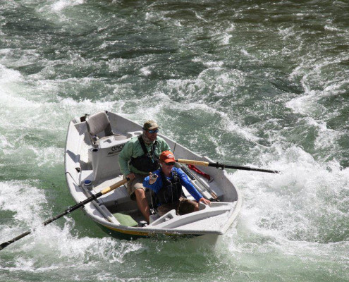 Fly fishing guide rows drift boat down rapids in the snake river wyoming
