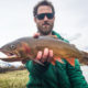 Fly fishing guide holding cutthroat trout in Jackson, Wyoming.