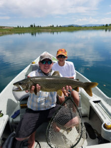 Fishing guide and client holding lake trout.