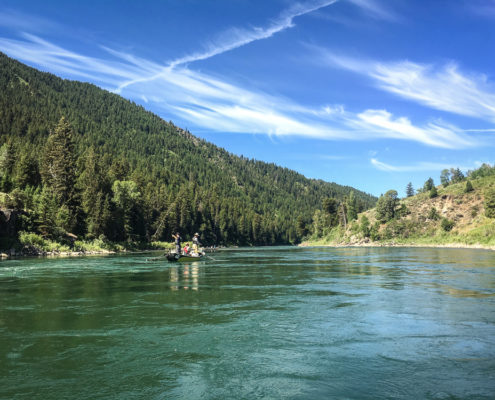 Drift boat floats down the snake river on a sunny day
